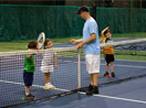 Tennis instructor teaching boys and girls